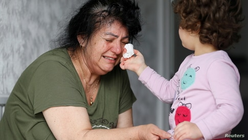 Ayse Mehmet, whose daughter Sonya Kaygan died from complications related to COVID-19, has tears wiped by her three-year-old granddaughter, also named Ayse, at her home in Enfield, Britain, April 27, 2020.