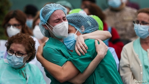 Health workers wearing protective face masks react during a tribute for their co-worker Esteban, a male nurse that died of complications related to COVID-19, outside the Severo Ochoa Hospital in Leganes, Spain, April 13, 2020.