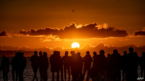 People gather at Southern Beach of Chigasaki to watch the sunrise on New Year's Day in Kanagawa Prefecture, southwest of Tokyo…