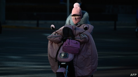 A woman wrapped up for the cold rides a motorcycle along a street on a winter day in Beijing on January 8, 2021 (Photo by WANG…