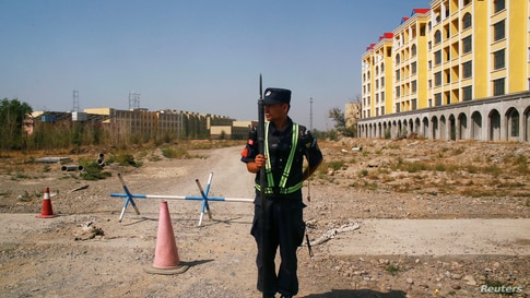 FILE - A Chinese police officer takes his position by the road near what is officially called a vocational education centre in Yining in Xinjiang Uighur Autonomous Region, China, Sept. 4, 2018.
