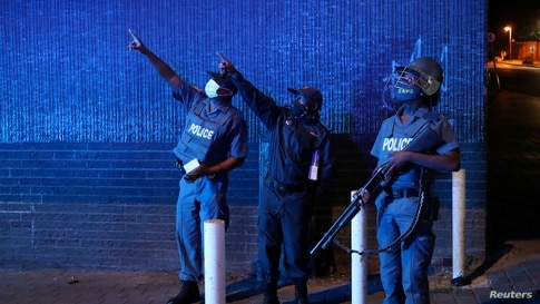 Police officers gesture during a patrol on New Year's day as a nighttime curfew is reimposed amid a nationwide coronavirus…