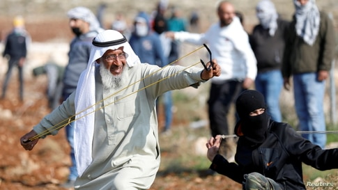 A Palestinian demonstrator uses a sling shot to hurl stones towards Israeli troops during a protest against Israeli settlements…