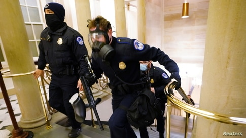 U.S. Capitol police officers take positions as protestors enter the Capitol building during a joint session of Congress.
