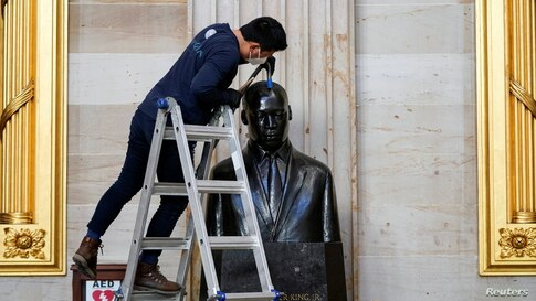 Gompo Yarmolinsky with the Architect of the Capitol cleans dust from the bust of Martin Luther King, Jr. in the Capitol Rotunda…