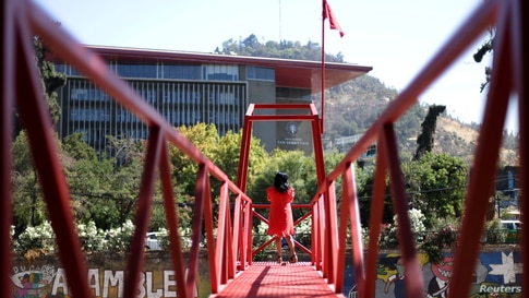 A woman stands at an urban intervention by chilean artist Ivan Navarro called 'Rio de sangre' (Blood river), a tribute to the…
