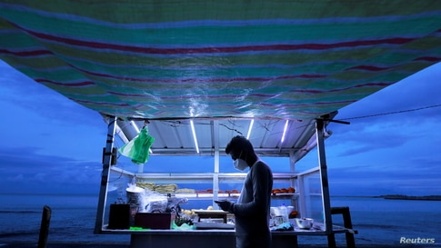 A street vendor wearing a face mask uses his mobile phone while waiting for customers at his food stall near a beach in Colombo…
