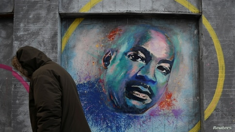 A person walks past a mural of Martin Luther King Jr. during the celebration of MLK Community Service Day in Washington D.C.,…