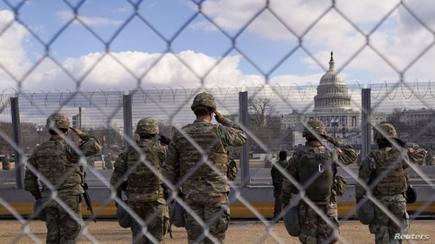National Guard members salute in front of the U.S. Capitol building during the inauguration of President-elect Joe Biden in…