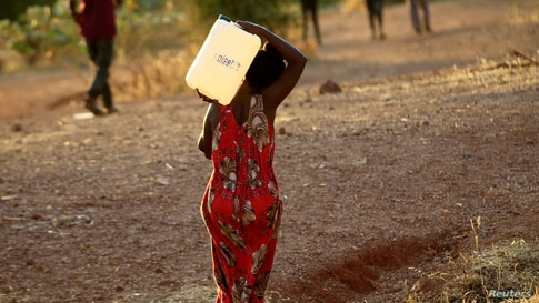 FILE PHOTO: An Ethiopian woman who fled war in Tigray region carries a jerrycan of water as she walks at the Um-Rakoba camp on…