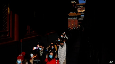 People wearing face masks to help curb the spread of the coronavirus visit Yonghegong Lama Temple as they offer prayers on the…