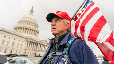Lloyd Watkins of Nashville, Tenn., a supporter of President Donald Trump carries a flag outside the Capitol, Jan. 5, 2021.