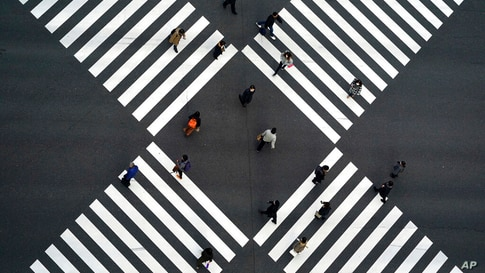 People wearing protective masks to help curb the spread of the coronavirus walk along pedestrian crossings in the Ginza…
