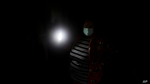 A woman holds up a light to illuminate inside of her house at the Canada Real shanty town, outside Madrid, Spain, Friday, Jan…