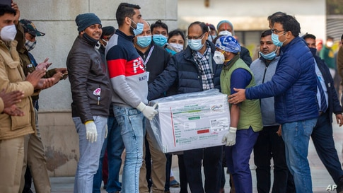 Health workers shift a box containing COVID-19 vaccine from a vehicle to a cold storage at Rajiv Gandhi Super Speciality…
