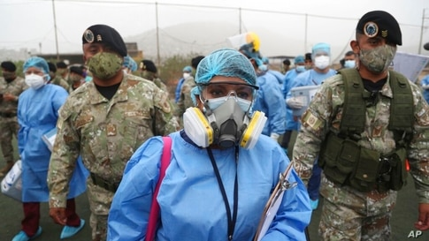 Health workers are escorted by soldiers during a house-to-house COVID-19 testing campaign in the Villa Maria del Triunfo…