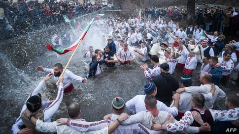 """Men perform the traditional """"Horo"""" dance in the icy winter waters of the Tundzha river in the town of Kalofer, as part of Epiphany Day celebrations despite the Covid-19 restrictions in the country."""