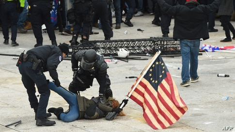 Police detain a person as supporters of President Donald Trump protest outside the U.S. Capitol, Jan. 6, 2021, in Washington, D.C.