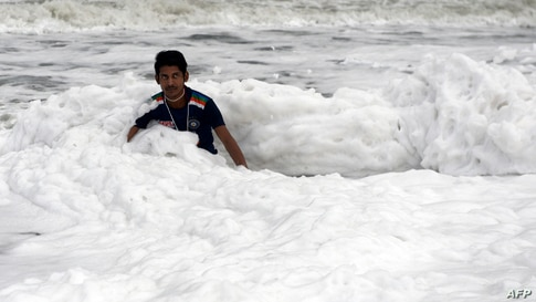 A man plays over foamy discharge caused by pollutants, as it mixes with the surf at Marina beach in Chennai, India.