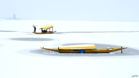 A boatman steers his boat at the partially frozen Dal Lake after a snowfall in Srinagar, India.