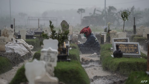 A man sits by the grave of a Covid-19 coronavirus victim amid pouring rain at Keputih cemetery in Surabaya, Indonesia.