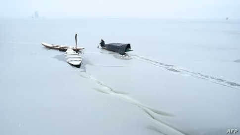 A boatman uses an oar to break the ice layer of the frozen portion of Dal Lake after heavy snowfall in Srinagar, India.