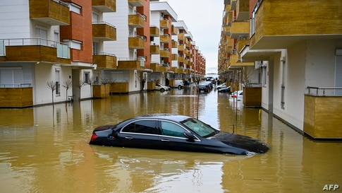 A car submerged on a flooded street in the town of Fushe Kosove after heavy rain and snow showers in Kosovo.