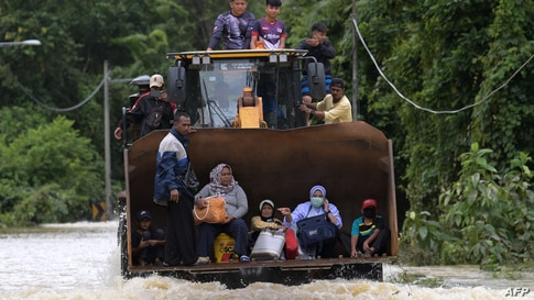 Residents ride a digger vehicle through floodwaters following heavy monsoon downpour in Lanchang, Malaysia's Pahang state.
