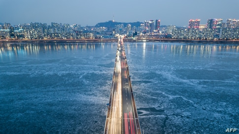 A general view of traffic passing over a bridge above the frozen Han river, before the Seoul city skyline, South Korea.