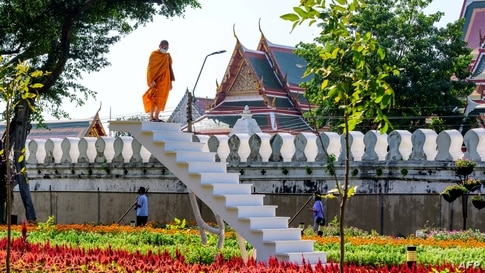 A Buddhist monk looks on from a staircase in the middle of a park in central Bangkok, Thailand.