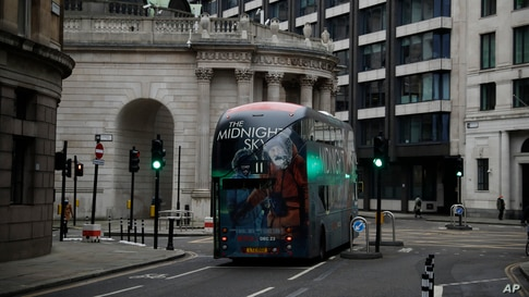 A bus drives through the City of London financial district in London, on the first morning of England entering a third national lockdown since the coronavirus outbreak began.
