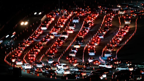 Motorists line up to take a coronavirus test in a parking lot at Dodger Stadium, Jan. 4, 2021, in Los Angeles.