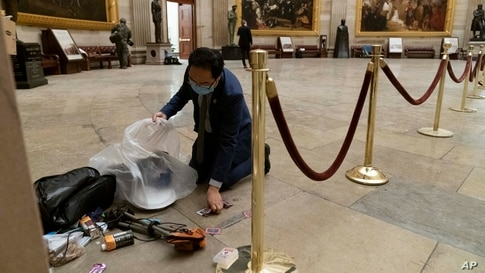 Rep. Andy Kim, D-N.J., cleans up debris and personal belongings strewn across the floor of the Rotunda after protesters stormed the Capitol on Jan. 6, 2021, in Washington.