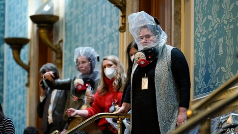 People shelter in the House gallery as protesters try to break into the House Chamber at the U.S. Capitol, Jan. 6, 2021, in Washington.