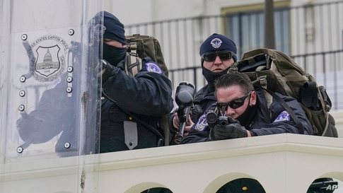 Police keep a watch on demonstrators who tried to break through a police barrier, Jan. 6, 2021, at the Capitol in Washington.