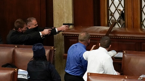 U.S. Capitol Police with guns drawn watch as protesters try to break into the House Chamber at the U.S. Capitol, Jan. 6, 2021, in Washington.