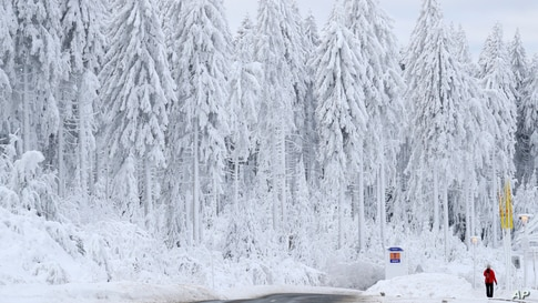 A man walks through a snow-covered landscape in Oberhof, Germany.