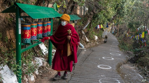 An exile Tibetan Buddhist monk rotates prayer wheels next to a path marked with circles for voters to ensure social distancing in Dharmsala, India.