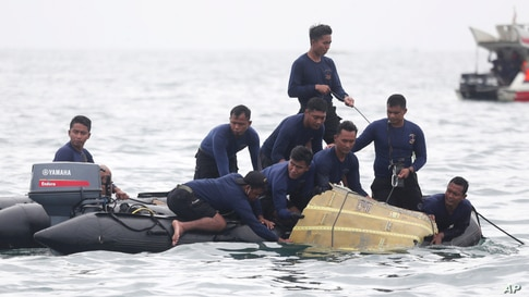 Indonesian Navy divers pull out a part of an airplane out of the water during a search operation for the Sriwijaya Air passenger jet that crashed into the sea near Jakarta.