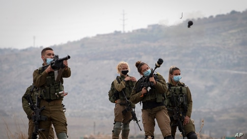 Israeli soldiers fire tear gas towards Palestinian demonstrators during a protest against the expansion of Israeli settlements near the West Bank village of Aqraba, north of Nablus.