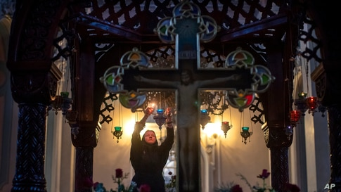 An Orthodox Church believer lights candles before the liturgy on Orthodox Christmas Eve in the Prechistensky, the Cathedral Palace in Vilnius, Lithuania.