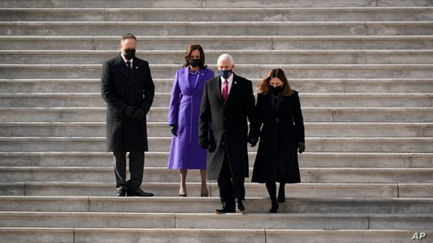 Vice President Kamala Harris and her husband Doug Emhoffl watch as former Vice President Mike Pence and his wife Karen Pence depart the Capitol after the inauguration ceremony of President Joe Biden at the Capitol in Washington, Jan. 20, 2021.