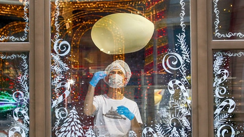 A cook in a face mask is seen making a pizza through a window glass decorated with Christmas ornaments in a city pizzeria in Kyiv, Ukraine.
