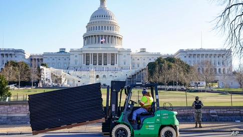 Workers place security fencing in place outside the mostly quiet Capitol in Washington, D.C.