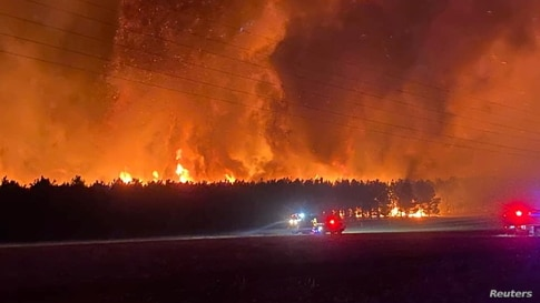 Smoke and flames from bushfire are seen in Gingin, Western Australia in this undated handout image. NIKKI WOODS/DEPARTMENT OF…