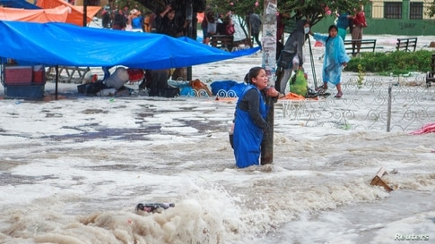 A woman clings to a lamp post during flooding caused by heavy rains in Sucre, Bolivia, Jan. 4, 2021.