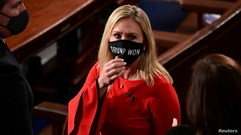 """U.S. Rep. Marjorie Taylor Greene (R-GA) wears a """"Trump Won"""" face mask as she arrives on the floor of the House to take her oath of office as a newly elected member of the 117th House of Representatives in Washington, D.C. Jan. 3, 2021."""