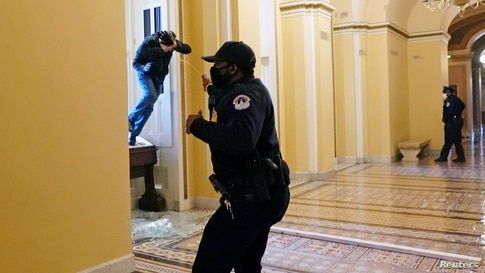 A U.S. Capitol police officer shoots pepper spray at a protestor attempting to enter the Capitol building during a joint session of Congress to certify the 2020 election results on Capitol Hill in Washington, Jan. 6, 2021.
