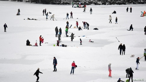 People ice-skate and play hockey on the frozen lake Spitzingsee as stricter lockdown measures are in place to contain the spread of the coronavirus disease (COVID-19) near the resort town of Schliersee, Germany.
