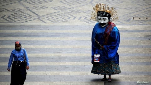"""A traditional large puppet figure known as """"Ondel-ondel"""", wearing a face mask, performs on a sidewalk in Jakarta, Indonesia."""